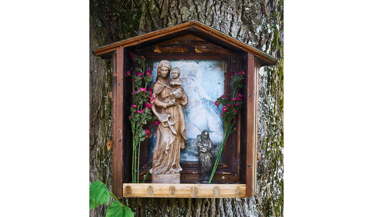 Blick auf ein Baumbild mit einer Heiligenfigur, seitlich Blumen