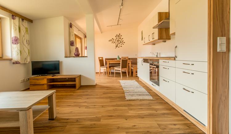Wohnbereich, seitlich mit einer Küche, Herd, im Hintergrund Essplatz mit Eckbank Tisch und Stühle, im Vordergrund Couchtisch Fernseher