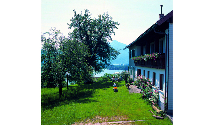 View of the holiday farm Mitterbauer, garden on the side with trees and sitting persons, in the background the lake. (© Pöllmann)