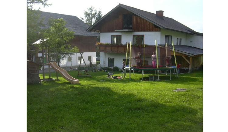 im Hintergrund das Haus, davor Trampolin mit Kindern, seitlich eine tusche, Schaukel, Wiese