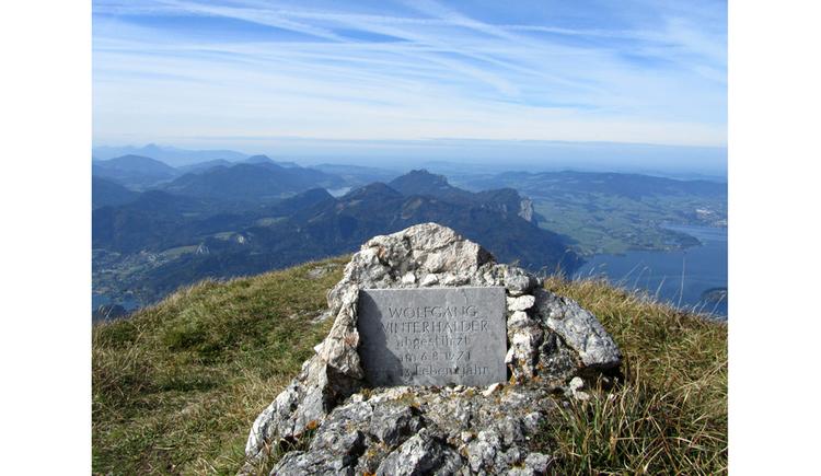 Blick auf eine Gedenktafel in einen Stein, im Hintergrund Berge, See