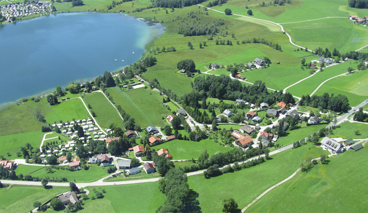 Aerial Photograph of the Camping place, surrounded by mealows and houses, in the background is the lake. (© Camping Moosmühle)
