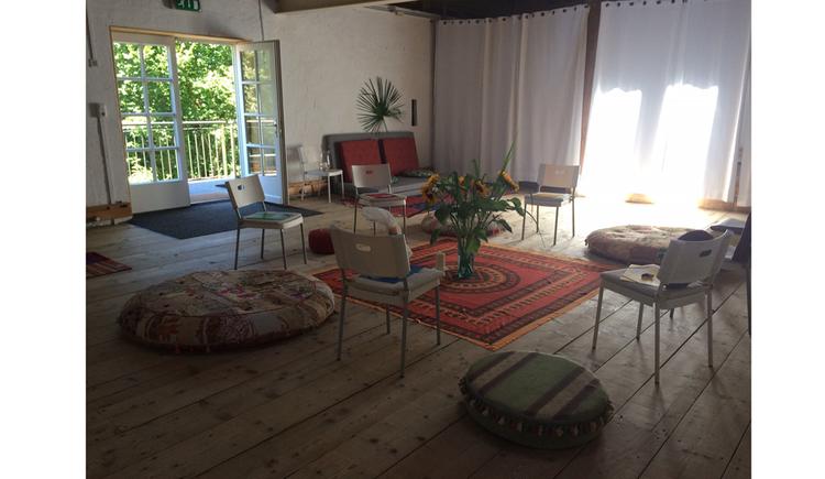 Raum mit Stühlen, Sitzkissen, in der Mitte ein Teppich mit großer Vase und Blumen, im Hintergrund Balkontüren