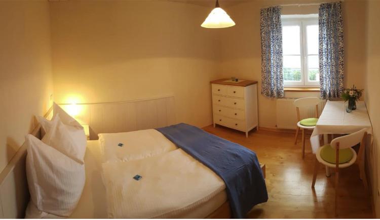 Doppelbett, im Hintergrund eine Kommode, Fenster, Tisch und Stühle