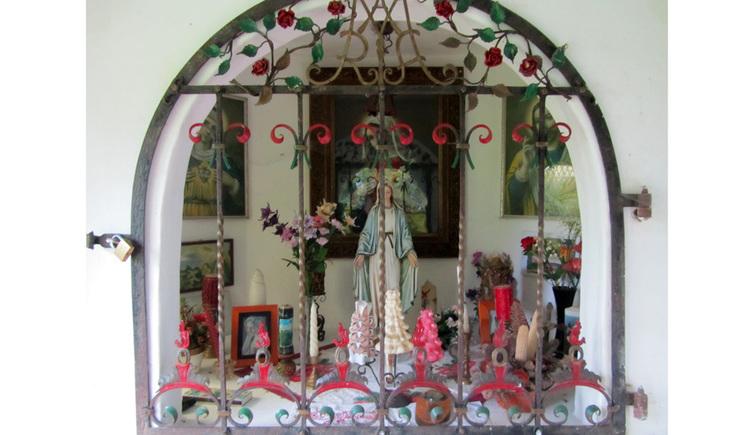 Blick auf den Altar hinter Gitter, Heiligenfigur, Kerzen