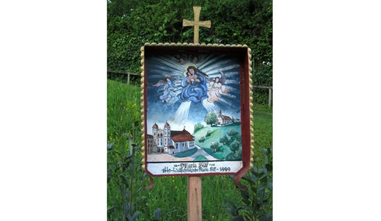 Blick auf ein bemaltes Bild, darauf ein kleines Kreuz