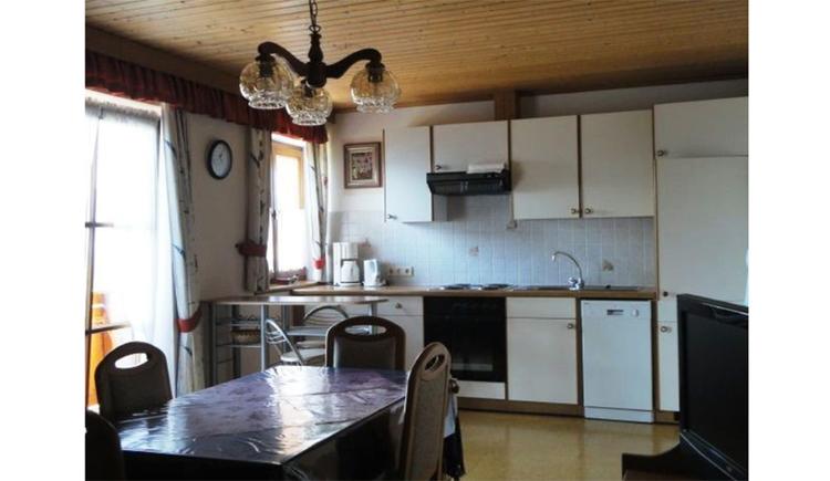 Küche mit Wasserkocher, Kaffeemaschine, Herd, seitlich ein Fernseher, gegenüber ein Tisch und Stühle, Balkontüre und Fenster