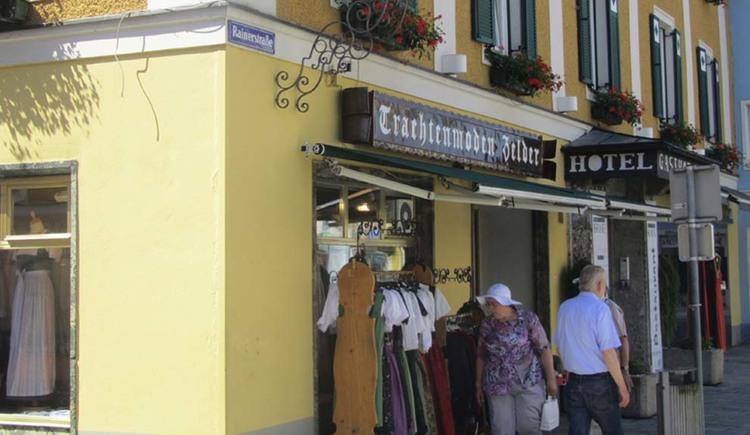 Blick auf das Geschäft, davor Personen, Kleiderständer