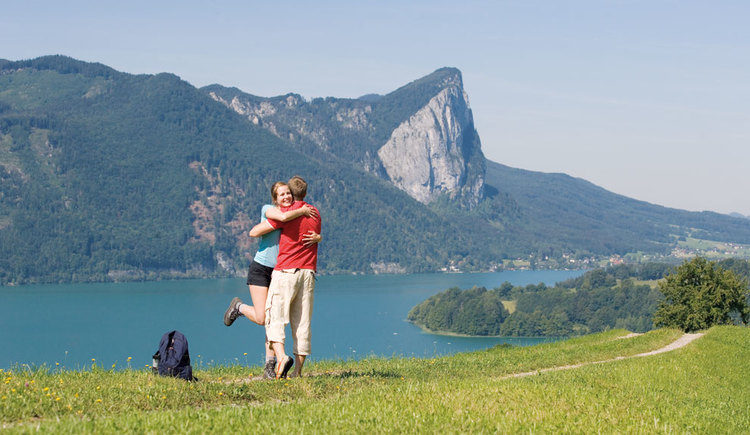 A couple in the foreground, lake Mondsee and the mountain Drachenwand in the background. (© www.mondsee.at)