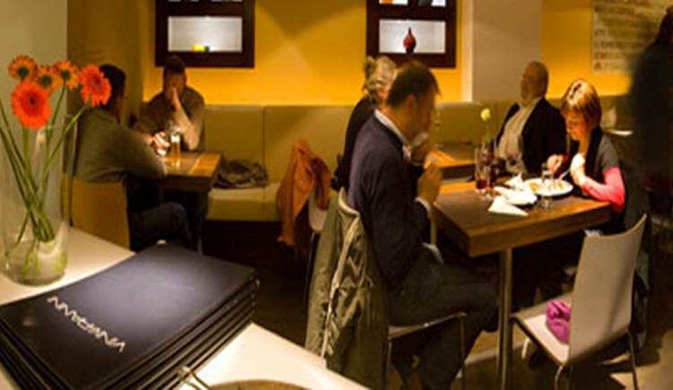 Innenbereich mit Tischen und Stühlen, im Vordergrund die Speisekarte und Blumen, im Hintergrund geselliges Beisammensein