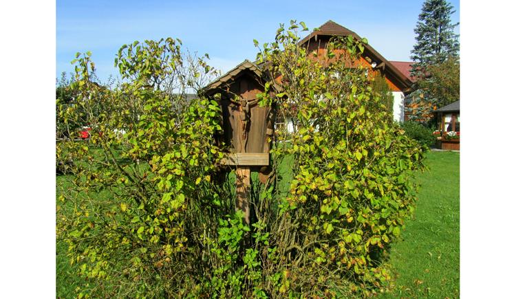 Blick auf ein Holzmarterl in einem Gebüsch, im Hintergrund Wiesen, Haus