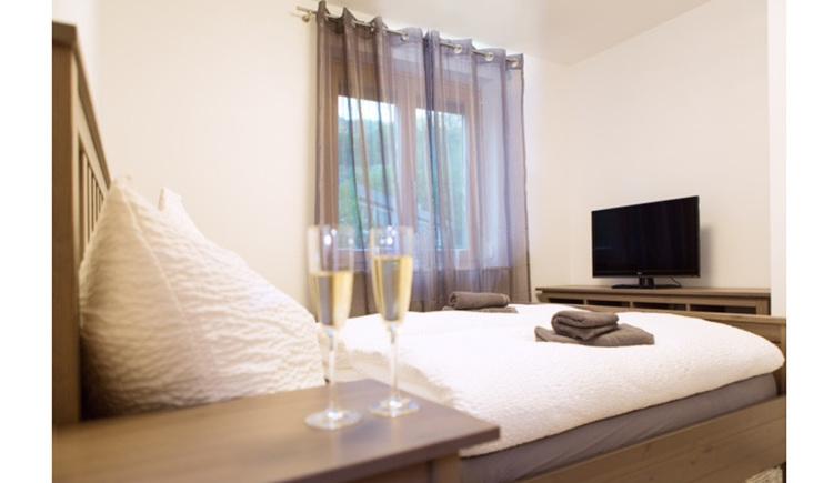 Schlafzimmer mit Doppelbett, im Hintergrund seitlich eine Fenster, Fernseher