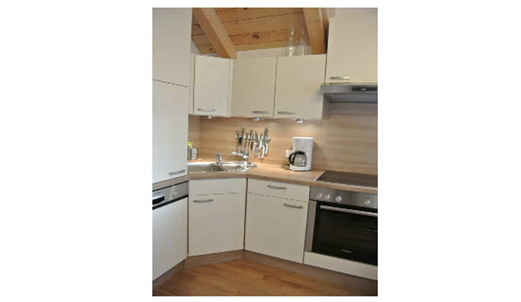look at the kitch with dishwasher, sink, coffee machine and cooker