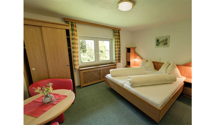 Double bed, in the front a table and chairs, on the side a wardrobe, window