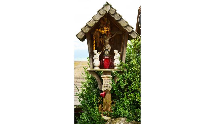 Blick auf das Holzkreuz im Figuren, Kerze, im Hintergrund Sträucher