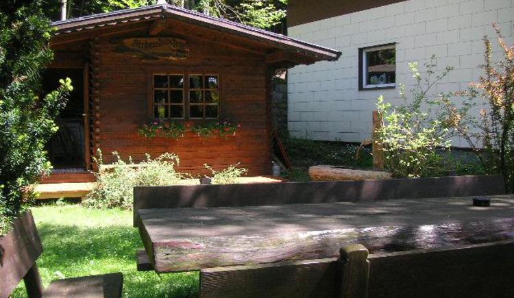 Holzhütte und -sitzgruppe im Garten