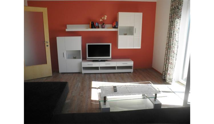 Wohnbereich mit Couch, Tisch, im Hintergrund eine Wohnwand mit Flat-TV, seitlich eine Balkontür