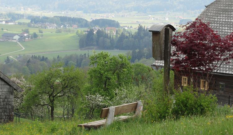 Bankerl in der Wiese, seitlich ein altes Haus, im Hintergrund Landschaft