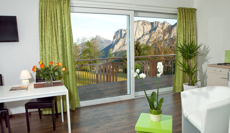 living room with table and chairs, TV hangs on the wall, in the background a balcony door, view at the scenery
