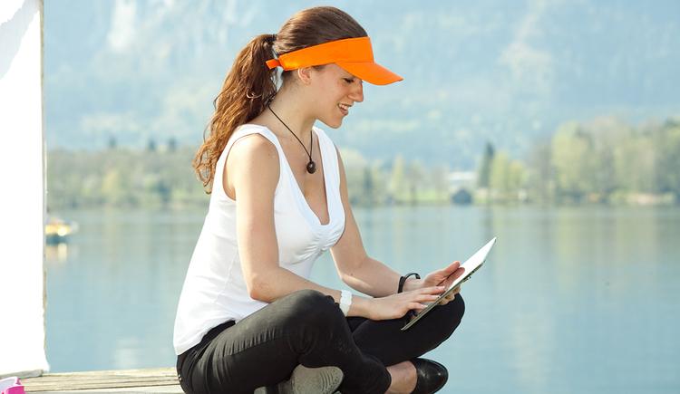 Person sitzt am Steg mit einem Tablet in der Hand, im Hintergrund der See