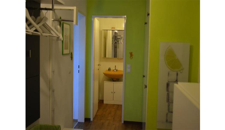 Blick vom Vorraum ins Badezimmer, mit Waschbecken und Spiegelschrank