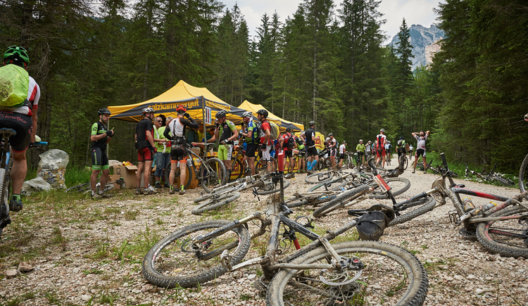 Many mountain bikers strengthen themselves at a refreshment station of the Mountainbike Trophy. (© Martin Bihounek)
