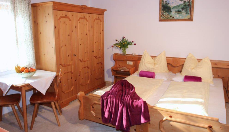 bedroom with double bed, wardrobe, table with chairs and a fruit bowl\n