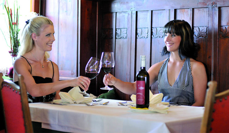 Damen sitzen gemütlich bei einem Glas Wein
