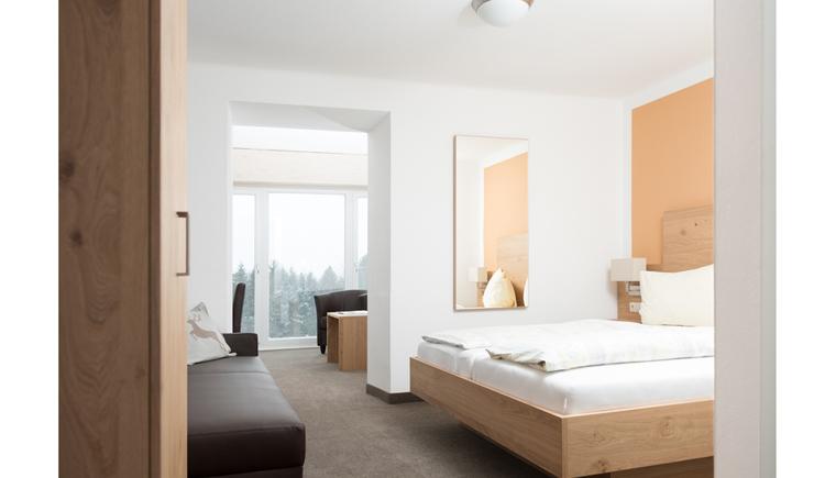 Doppelbett, im Hintergrund große Fensterfronten