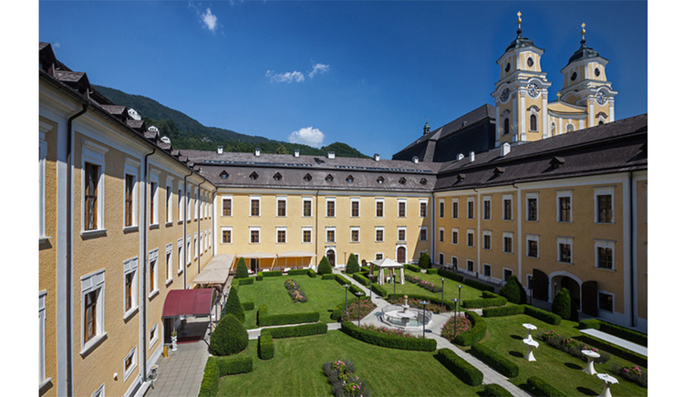 View of the Castle Mondsee, in the background the towers of the church - St. Michael's Basilica, courtyard - palace garden with fountain