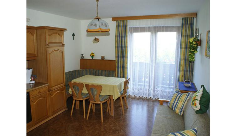 Wohnbereich: im Hintergrund eine Eckbank mit Tisch und Stühle, Balkontür, seitlich im Vordergrund eine Couch mit Polster, gegenüber ein Teil von der Küche