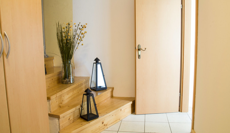 Brightly furnished entrance area with wooden staircase