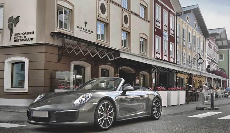 ein Blick von außen auf das Hotel mit Gastgarten, im Vordergrund ein Cabrio. (© Iris Porsche Hotel & Restaurant)