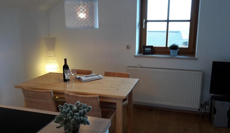Essbereich mit Tisch und Stühle, im Hintergrund ein Fenster