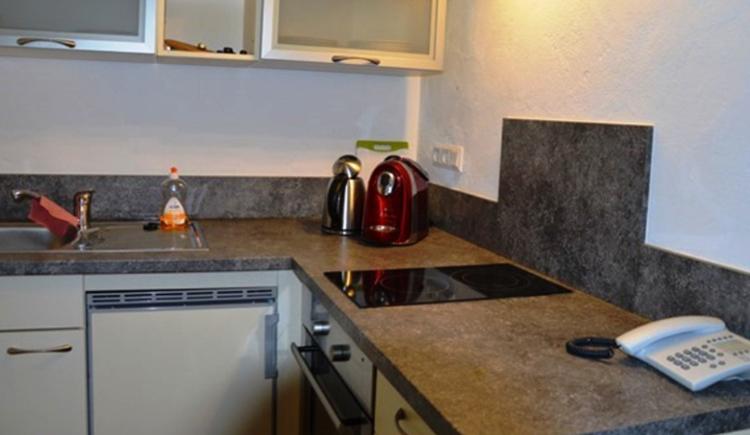 Küche mit Herd, Kaffeemaschine, Wasserkocher, im Vordergrund befindet sich ein Telefon