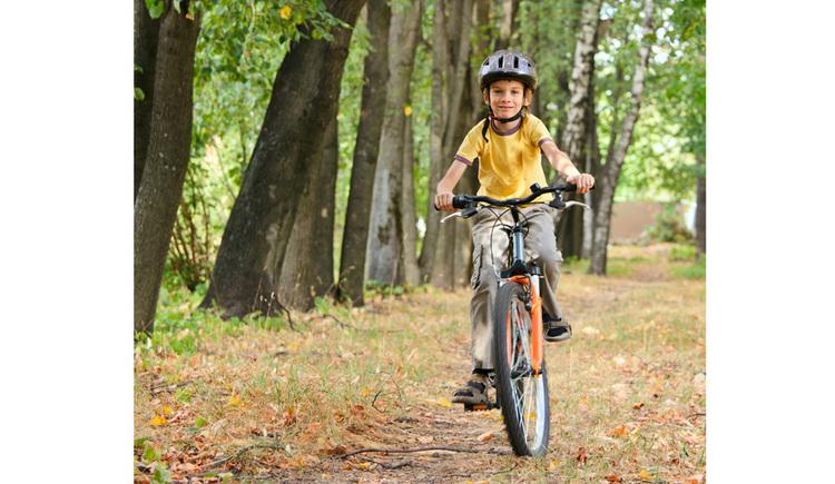 Kinder beim Radfahren, im Hintergrund und seitlich Bäume