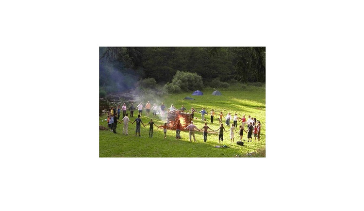 persons stand in a circle around a campfire\n\n