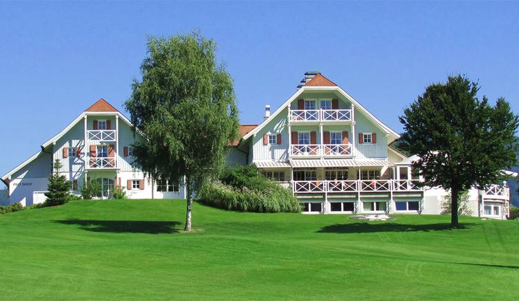 Blick auf die Villa, im Vordergrund Bäume und eine Wiese