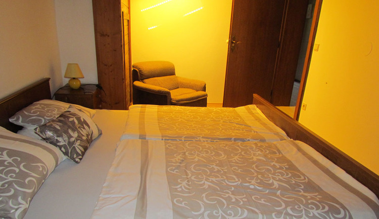 Room with double bed and chair