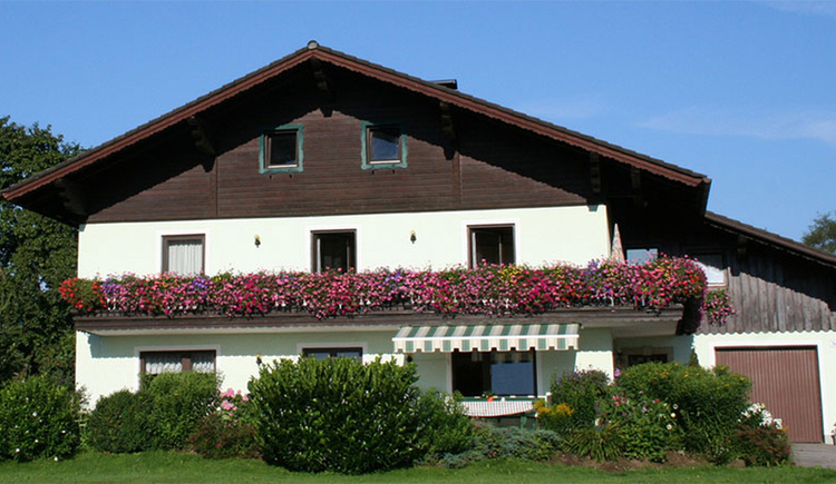 View of the house with balcony and flowers, awning, in the foreground shrubs and meadows