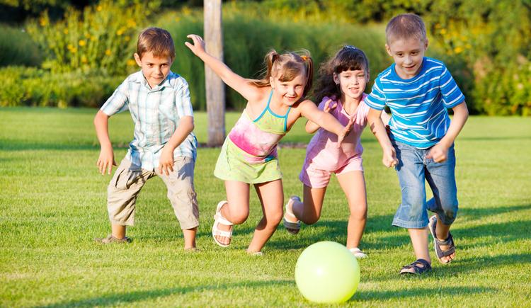 spielende Kinder in der Wiese, Ball im Vordergrund