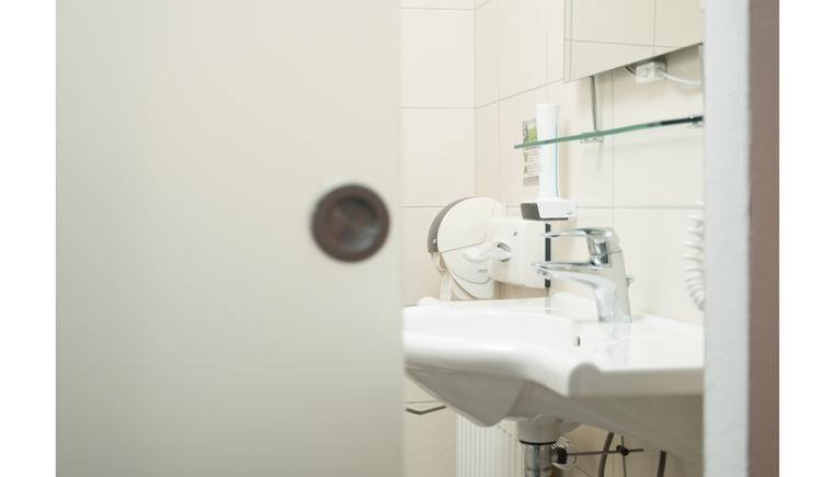 Blick durch eine offene Schiebetür ins Badezimmer, Waschbecken