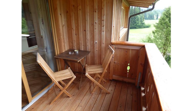 Balkon mit Sitzecke und rechts Blick ins Grüße