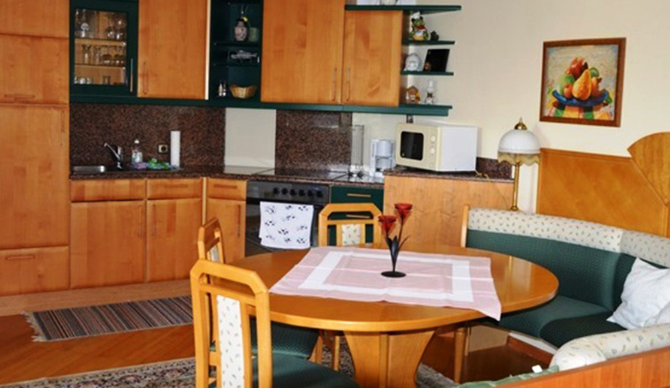 kitchen with cooker, microwave, coffee machine, place to eat with corner bench, table and chairs, on the table is a candle-holder