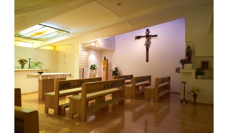 Holzbänke, Kreuz an der Wand