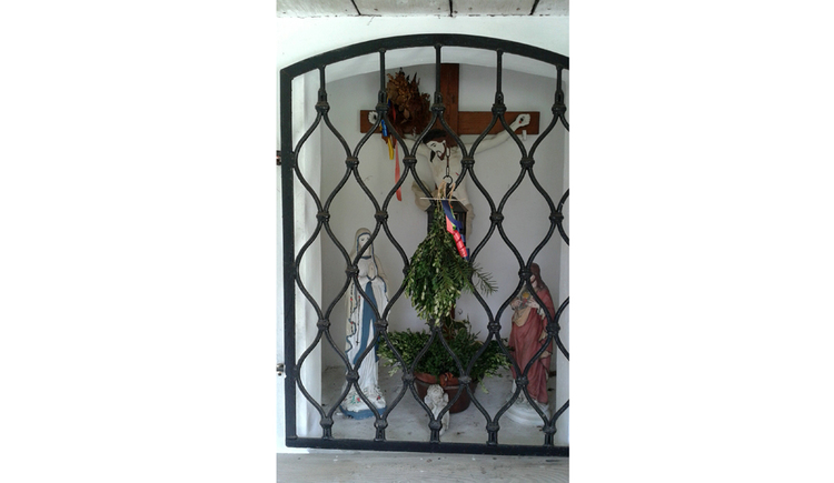 Hinter Gitter befindet sich ein Kreuz, Blumen, Statuen