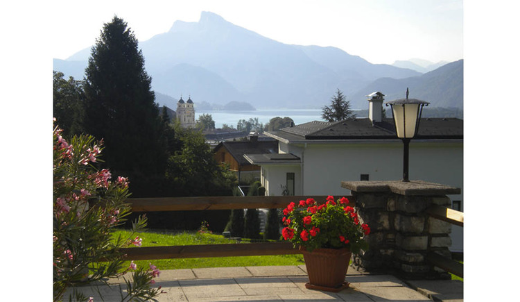 Terrace with flowers, lake and mountains in the background