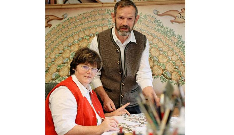 Stammbaummalerin Regina sitzt am Schreibtisch, ihr Mann, Stammbaummaler Franz steht hinter ihr.