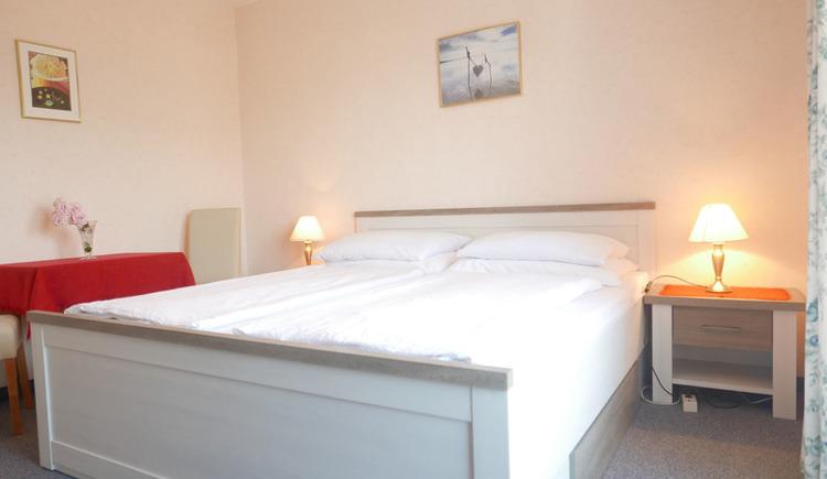 Schlafzimmer mit Doppelbett, Nachtkästchen mit Tischlampen, Tisch mit Stühlen