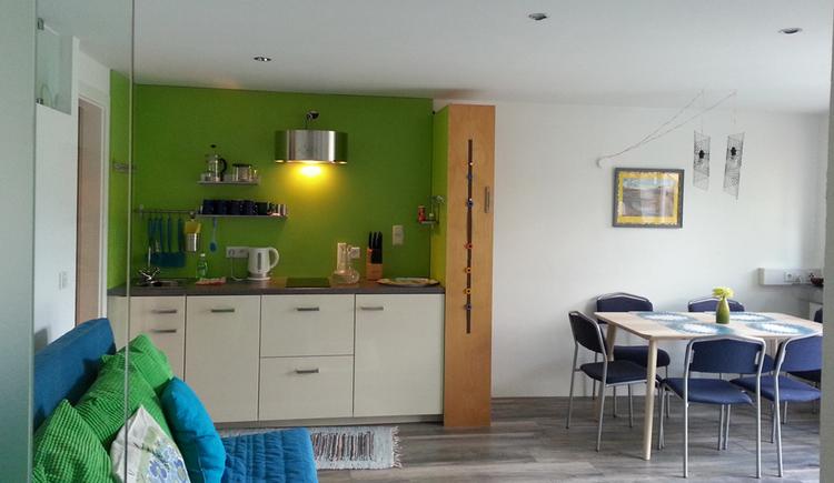 Blick in die Küche mit Wasserkocher, Messerblock, seitlich der Essbereich mit Tisch und Stühlen.